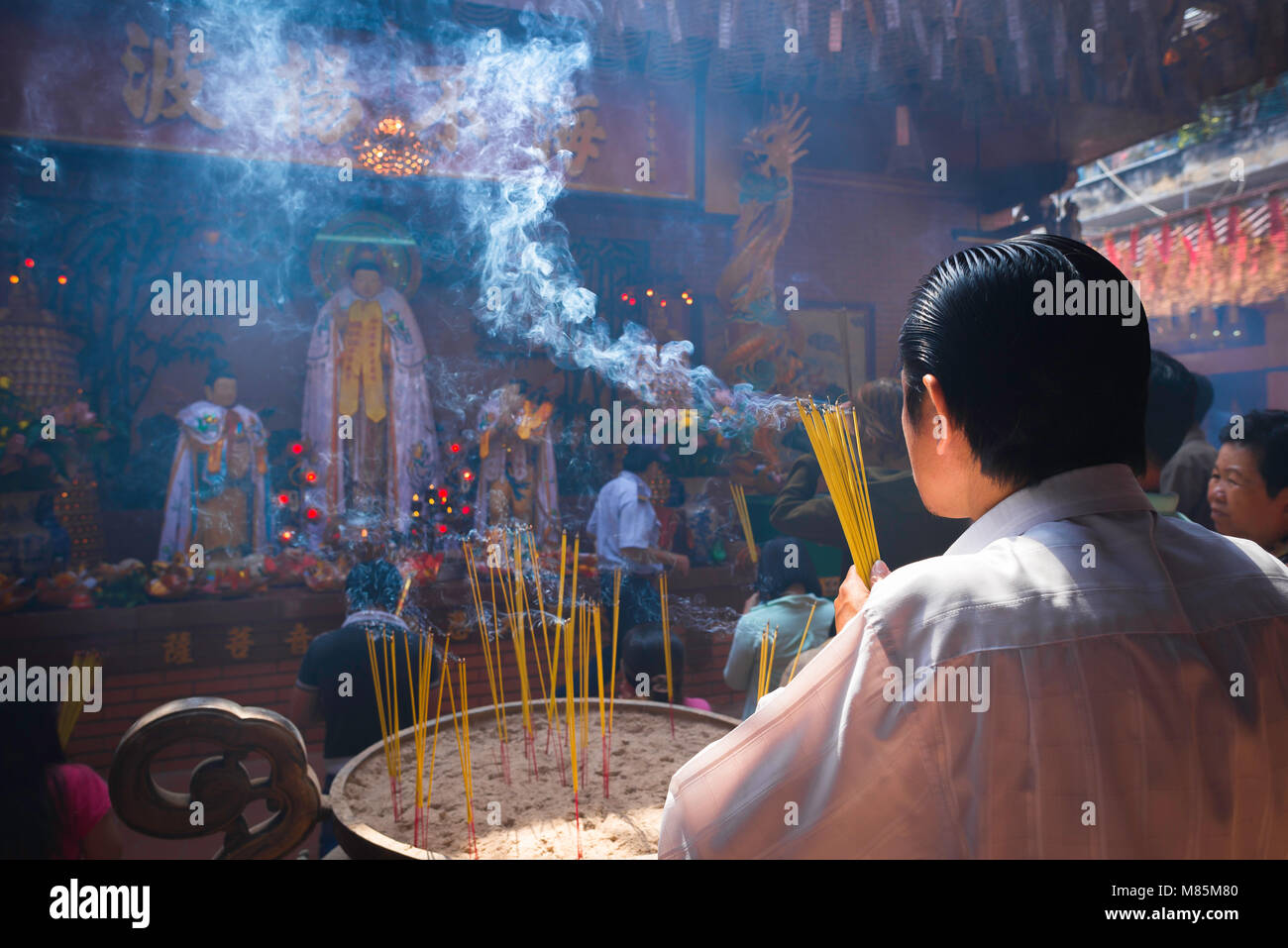 Man prayer Southeast Asia, rear view of a man praying in the Quan Am pagoda - temple - in the Cholon area of Ho - Stock Image