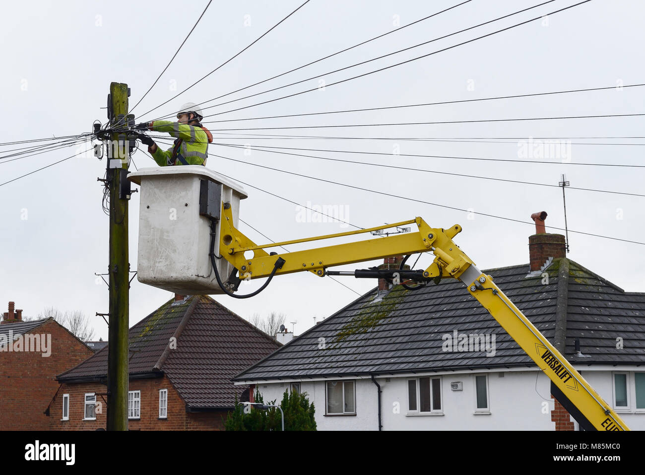 A BT Openreach engineer working on telephone cables from a cherry picker - Stock Image