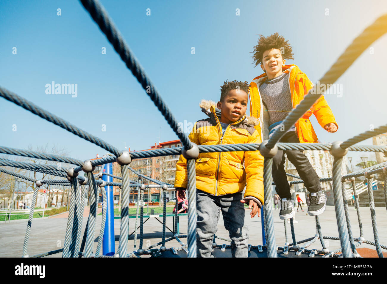 Two children with yellow coats jumping on elastic bed in a playground in a sunny day Stock Photo