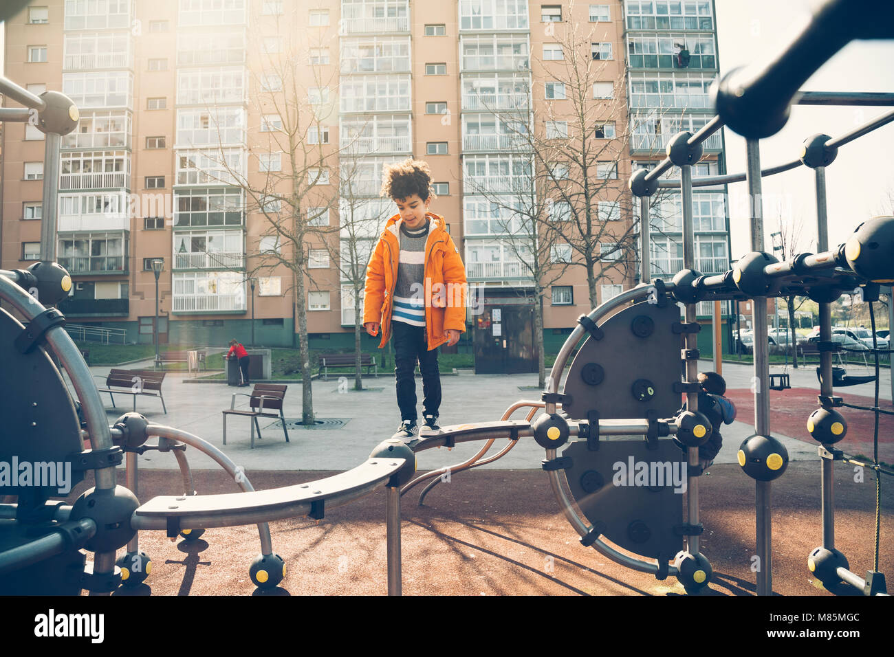 Cute little boy walking the balance bar in an urban playground in a sunny day - Stock Image