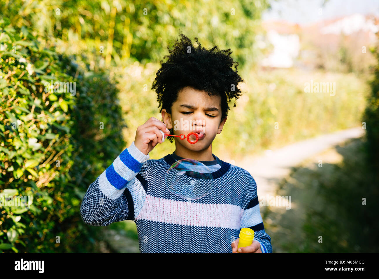Little boy blowing bubbles on a path in the garden on a sunny day Stock Photo