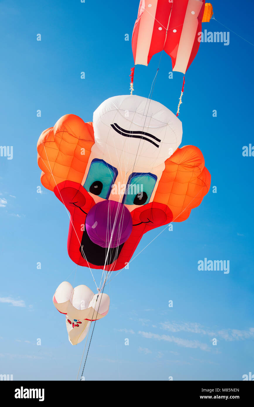 a kite in the shape of a clown face flying on the blue sky Stock Photo