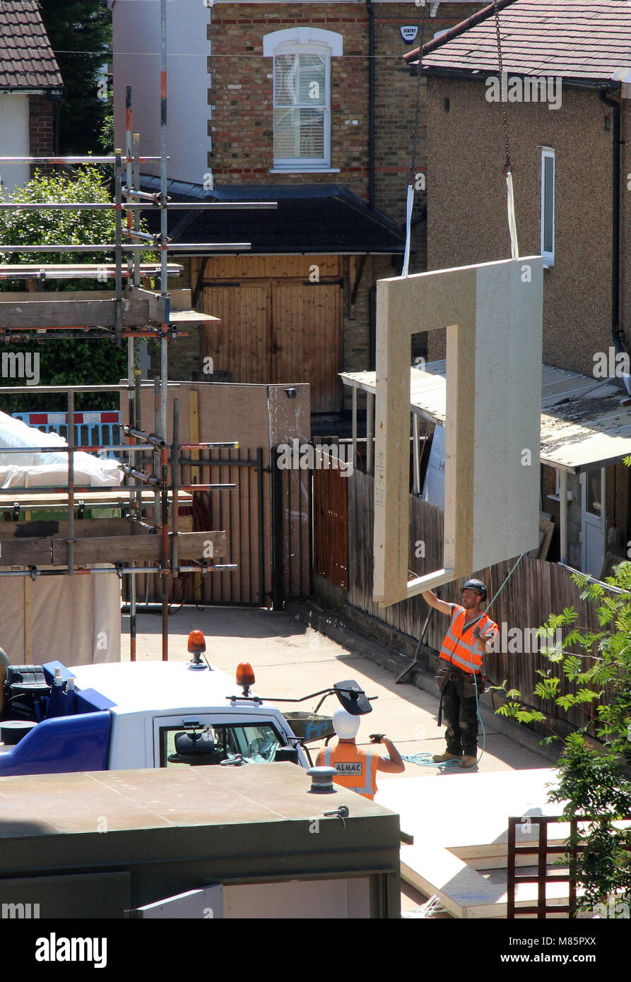 Builders Hoisting a Structural Insulated Panel (SIP) - Stock Image