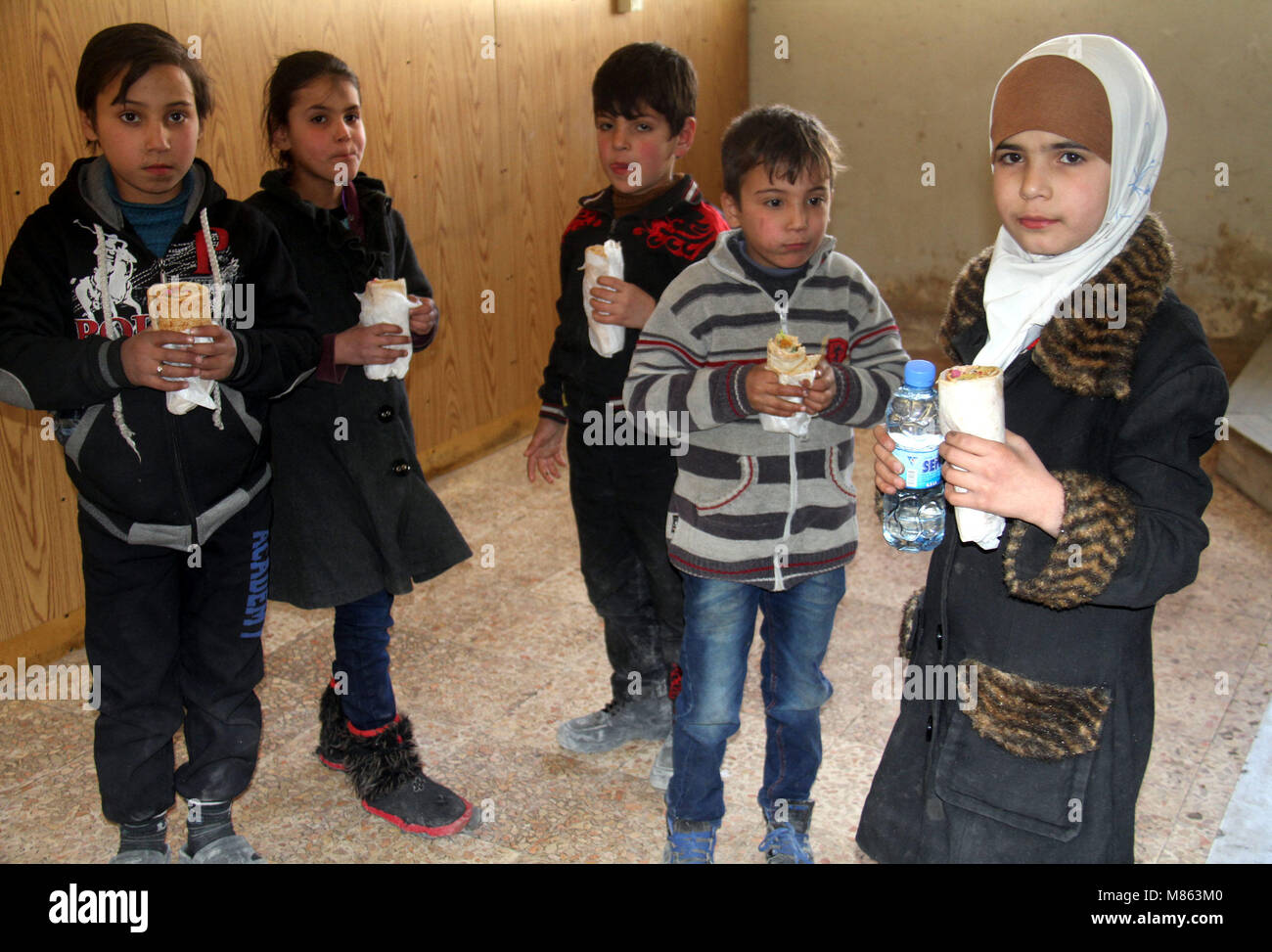 Damascus. 14th Mar, 2018. Evacuated children eat food at a temporary shelter in the Wafidin area in northeast Damascus - Stock Image