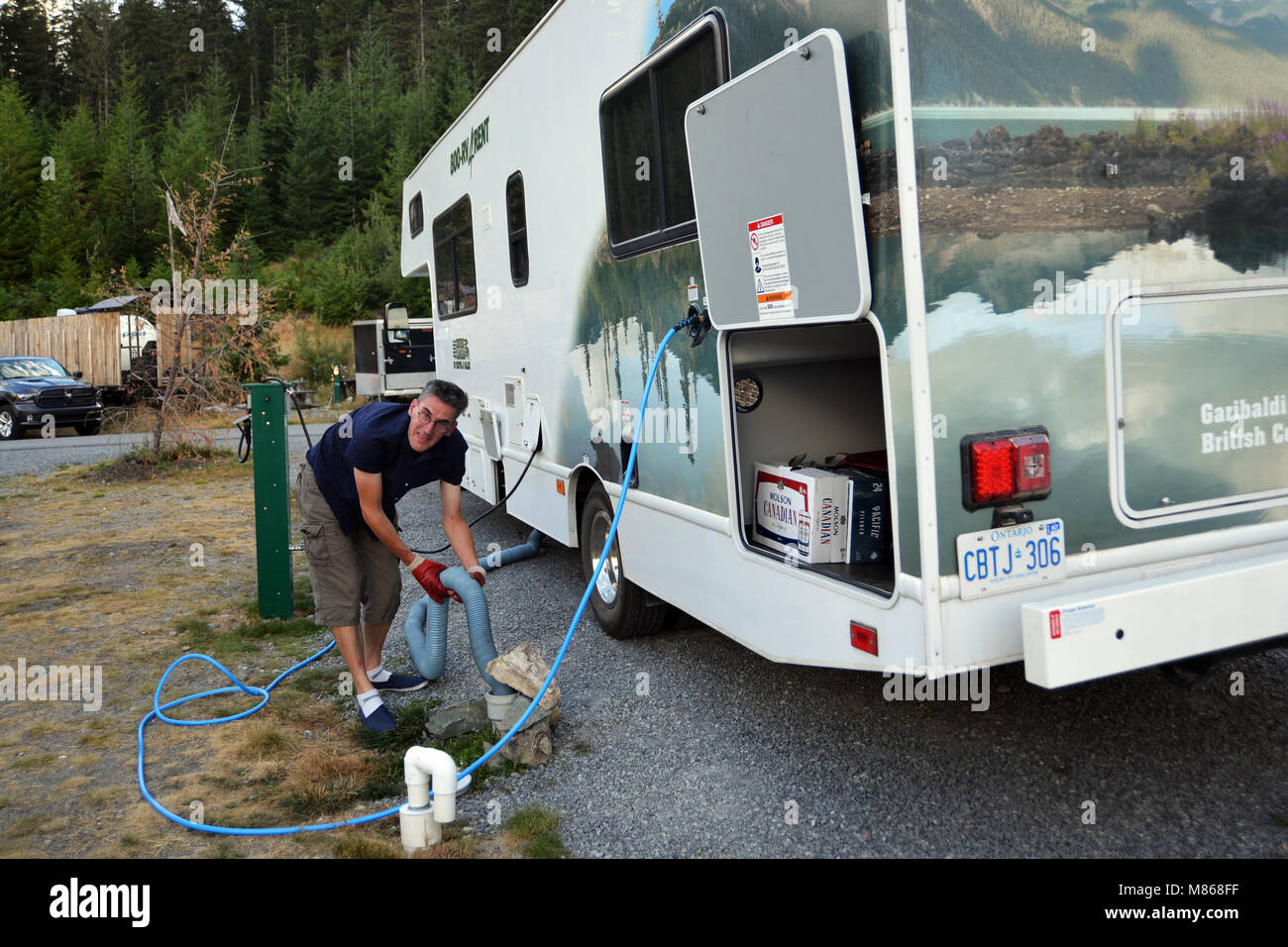 RV vacation Canadian Rockies, Canada man empties dump tank on  holiday model released - Stock Image