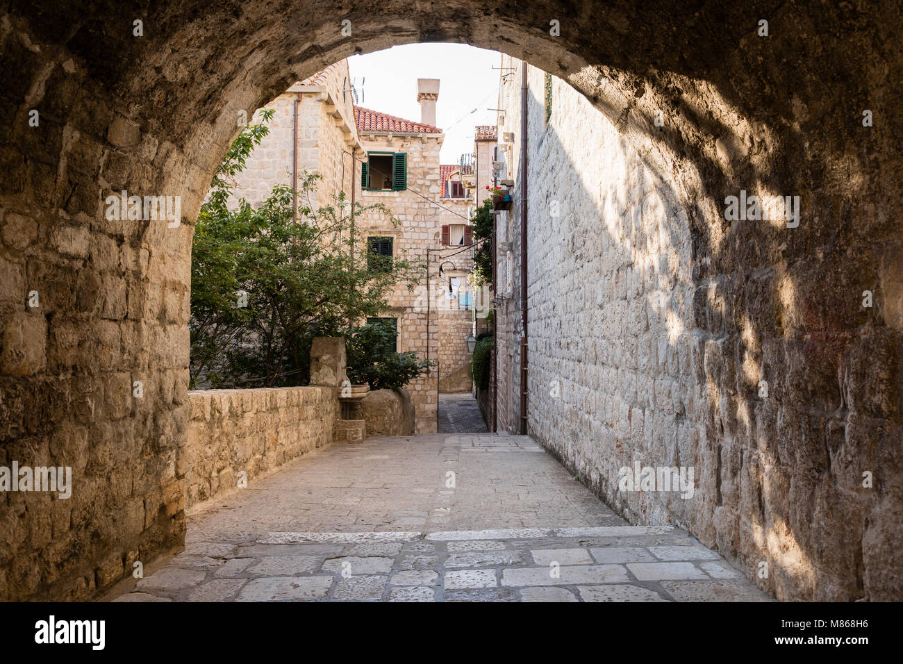 View from an arched bridge onto residential houses in historic Dubvronik in the morning light - Stock Image