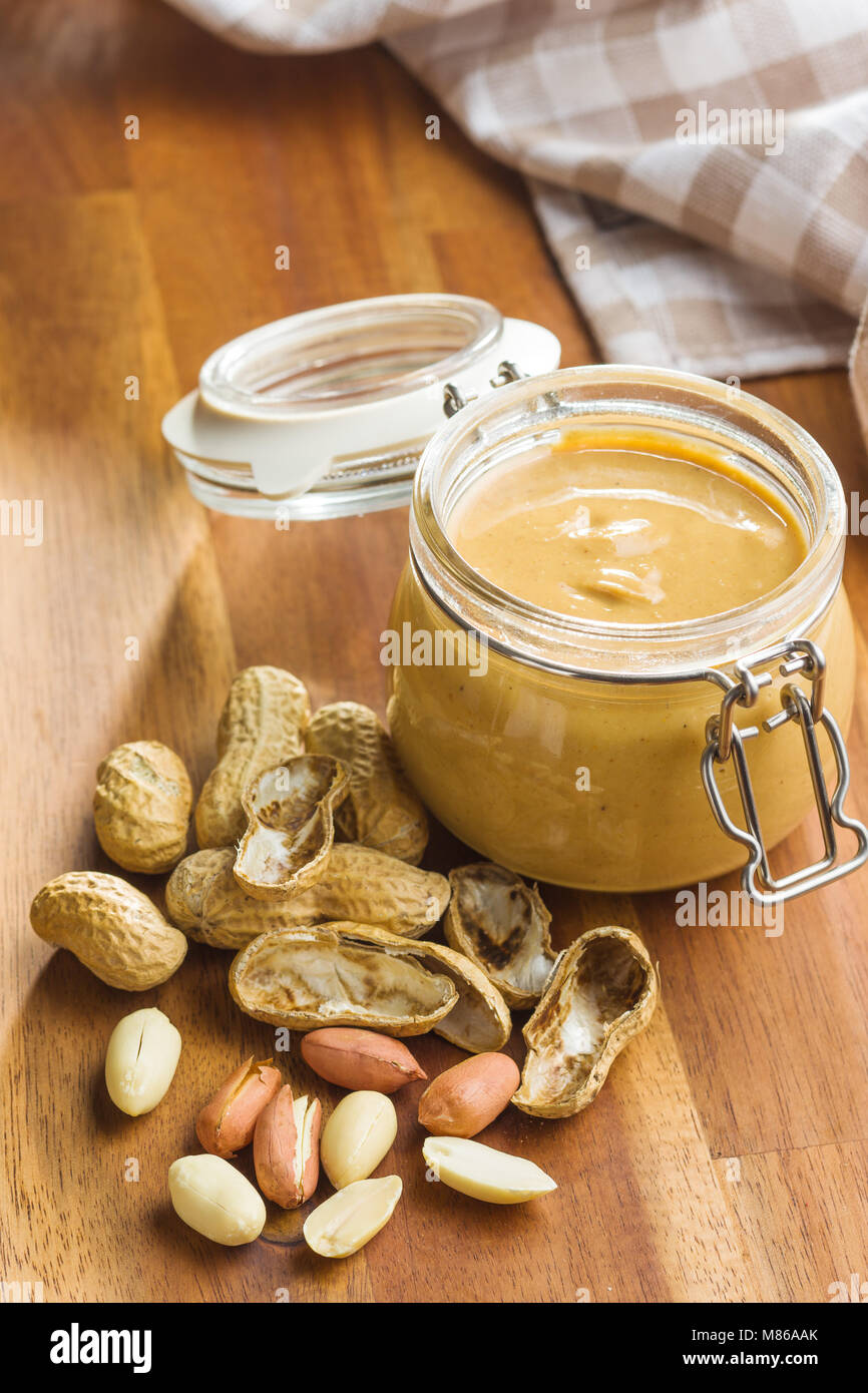Peanut butter in jar and peanuts on wooden table. - Stock Image