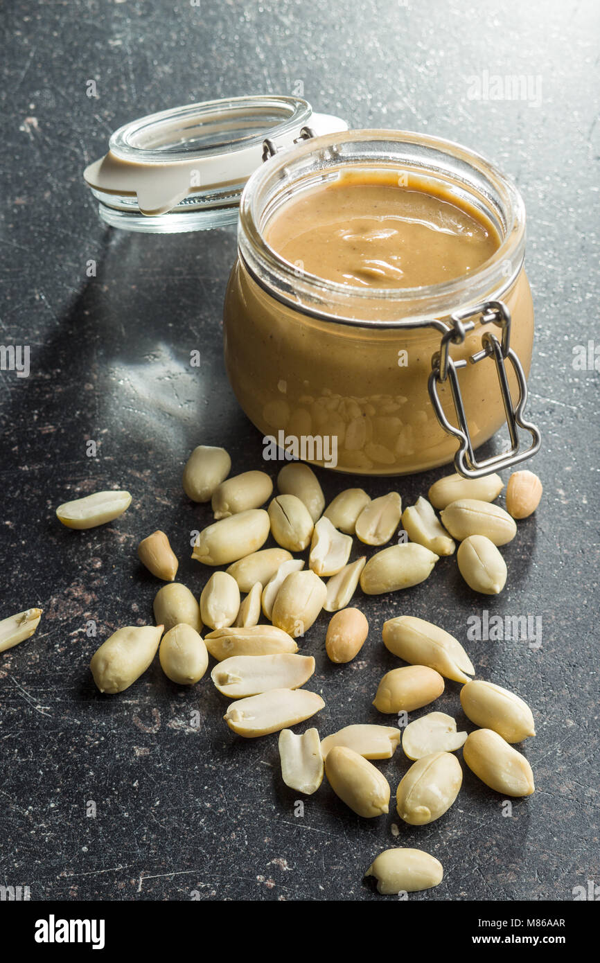 Peanut butter in jar and peanuts on old kitchen table. - Stock Image