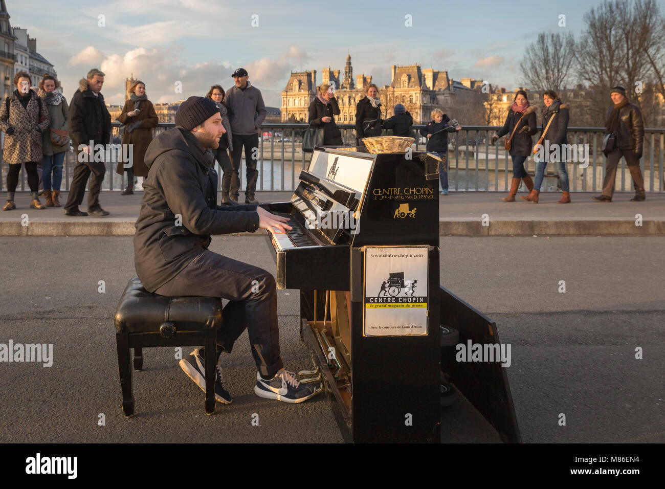 Street muscian Louis Artson playing a piano  on Pont Saint Louis in Paris, France.  Advertising on the side of the - Stock Image