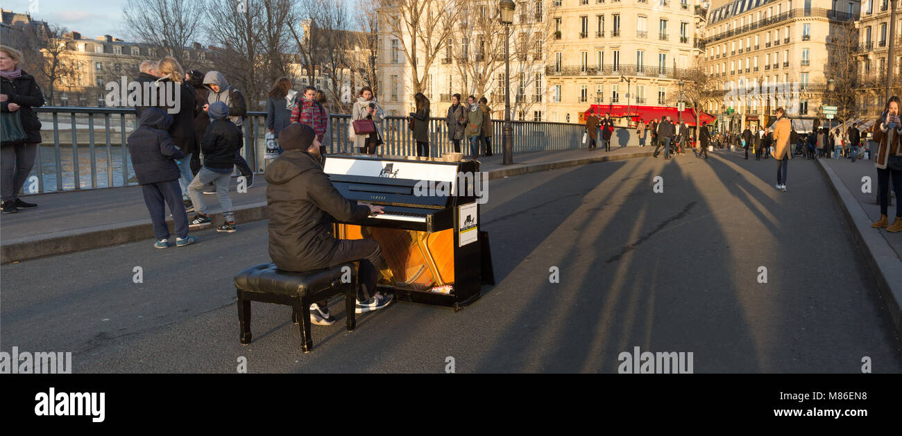 Pianist Louis Artson preforming on a Yamaha piano on the Pont Saint Louis in Paris, France. - Stock Image