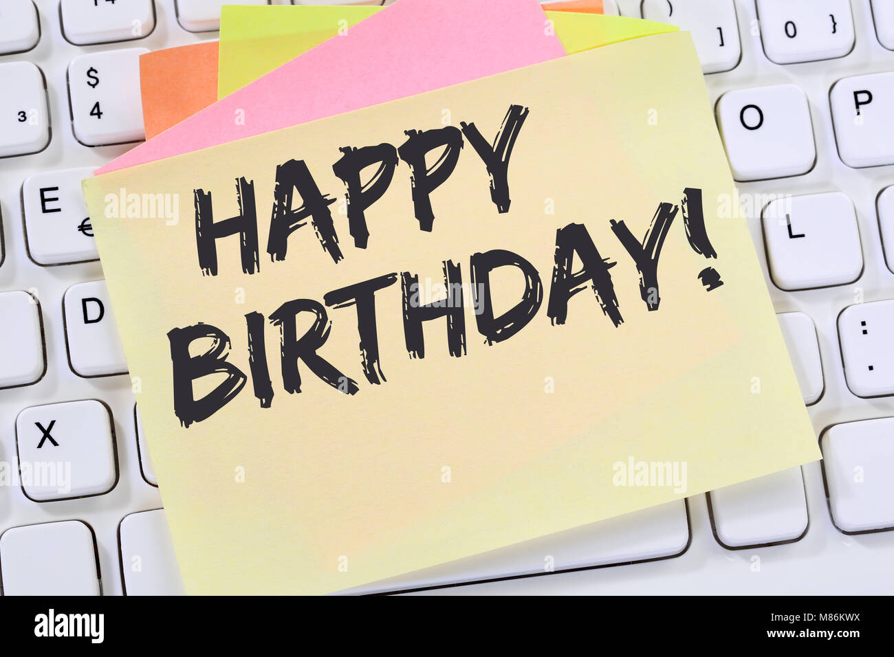 Happy Birthday greetings celebration business note paper computer keyboard - Stock Image