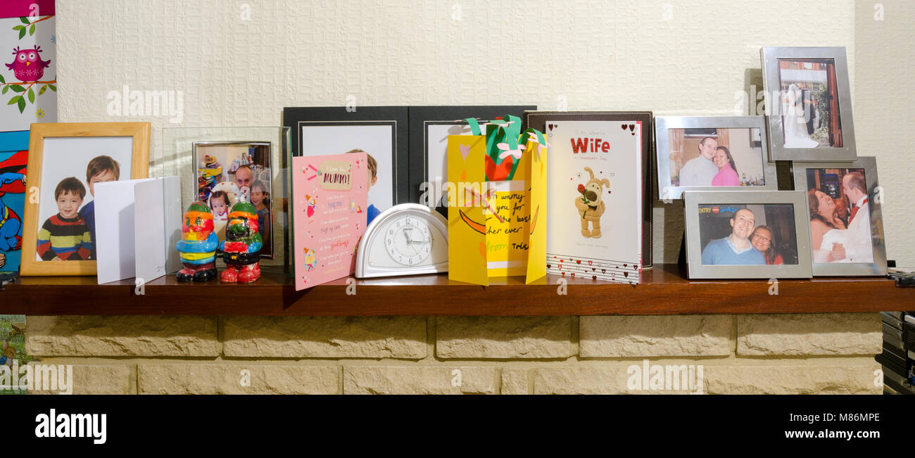 A mantelpiece with a clock, family photos and mother's day cards. - Stock Image