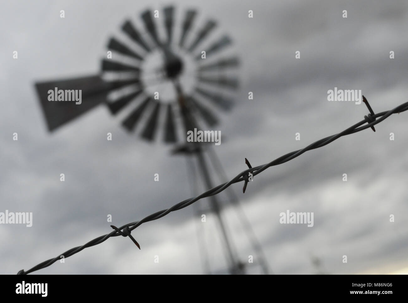 An old-fashioned windmill stands behind a barbed wire fence along a ...