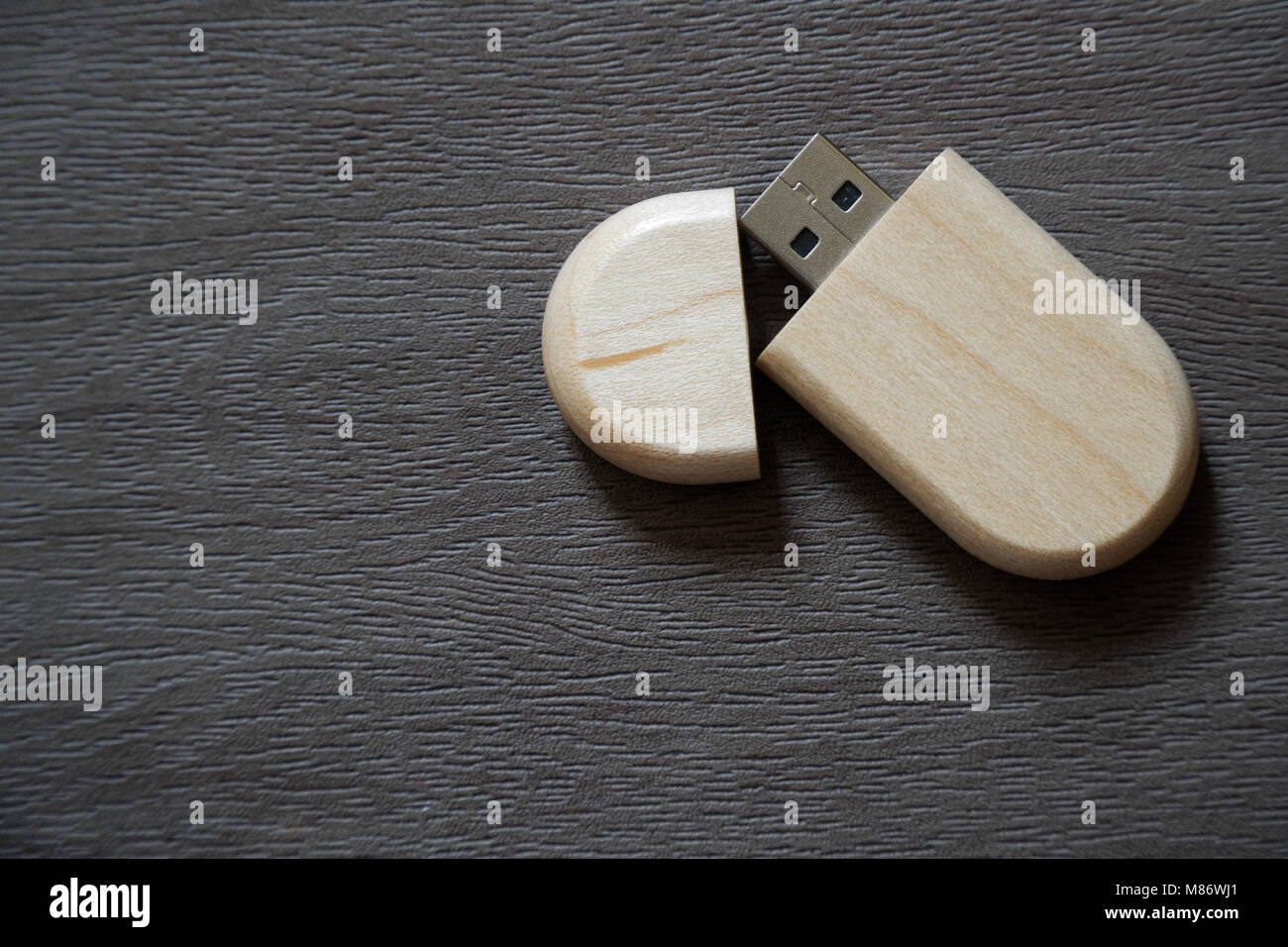 Usb flash drive with wooden surface on desk for USB port plug-in computer laptop for transfer data and backup business - Stock Image