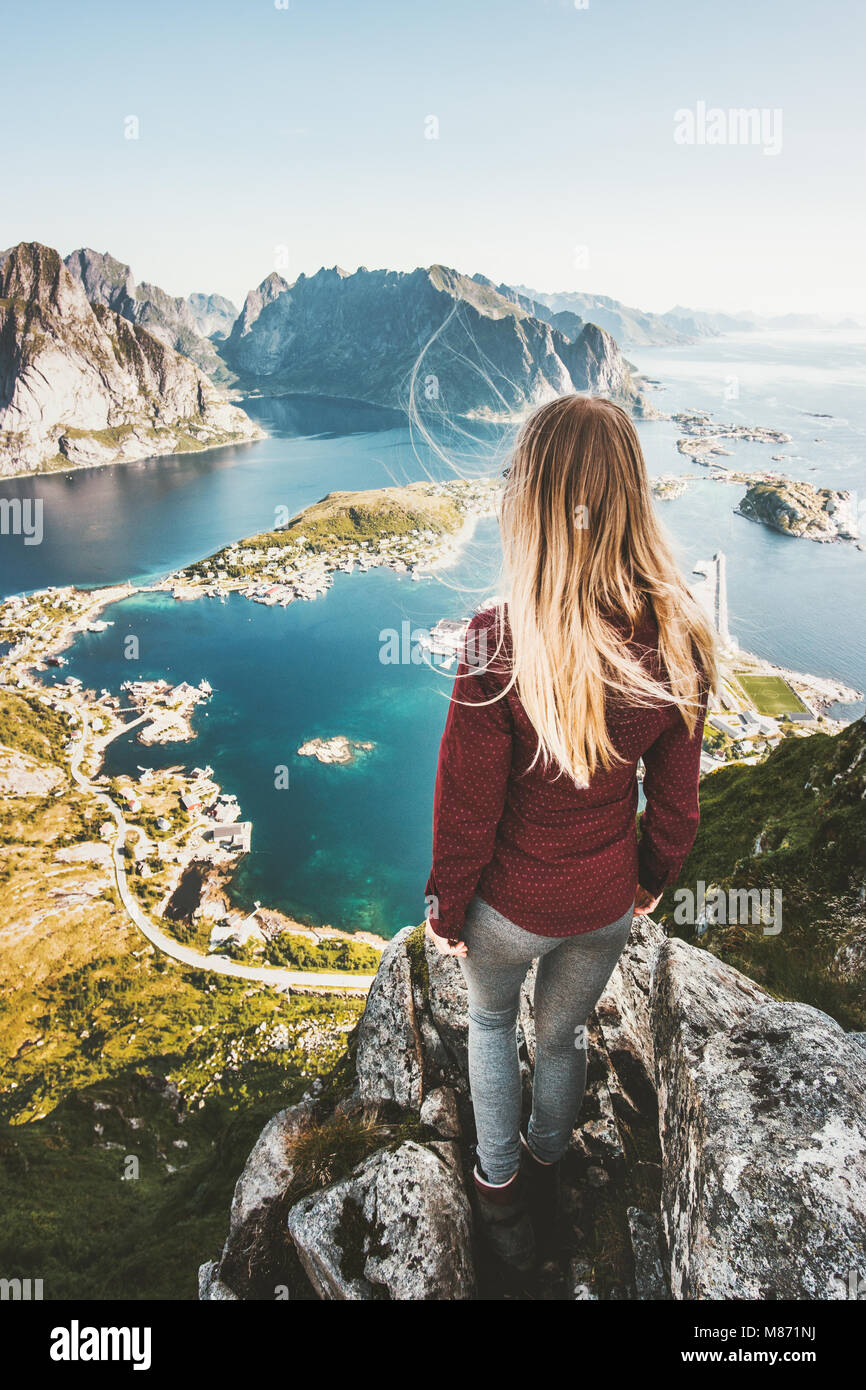 Woman tourist traveling in Norway standing on cliff mountain aerial view Lofoten islands lifestyle exploring concept - Stock Image