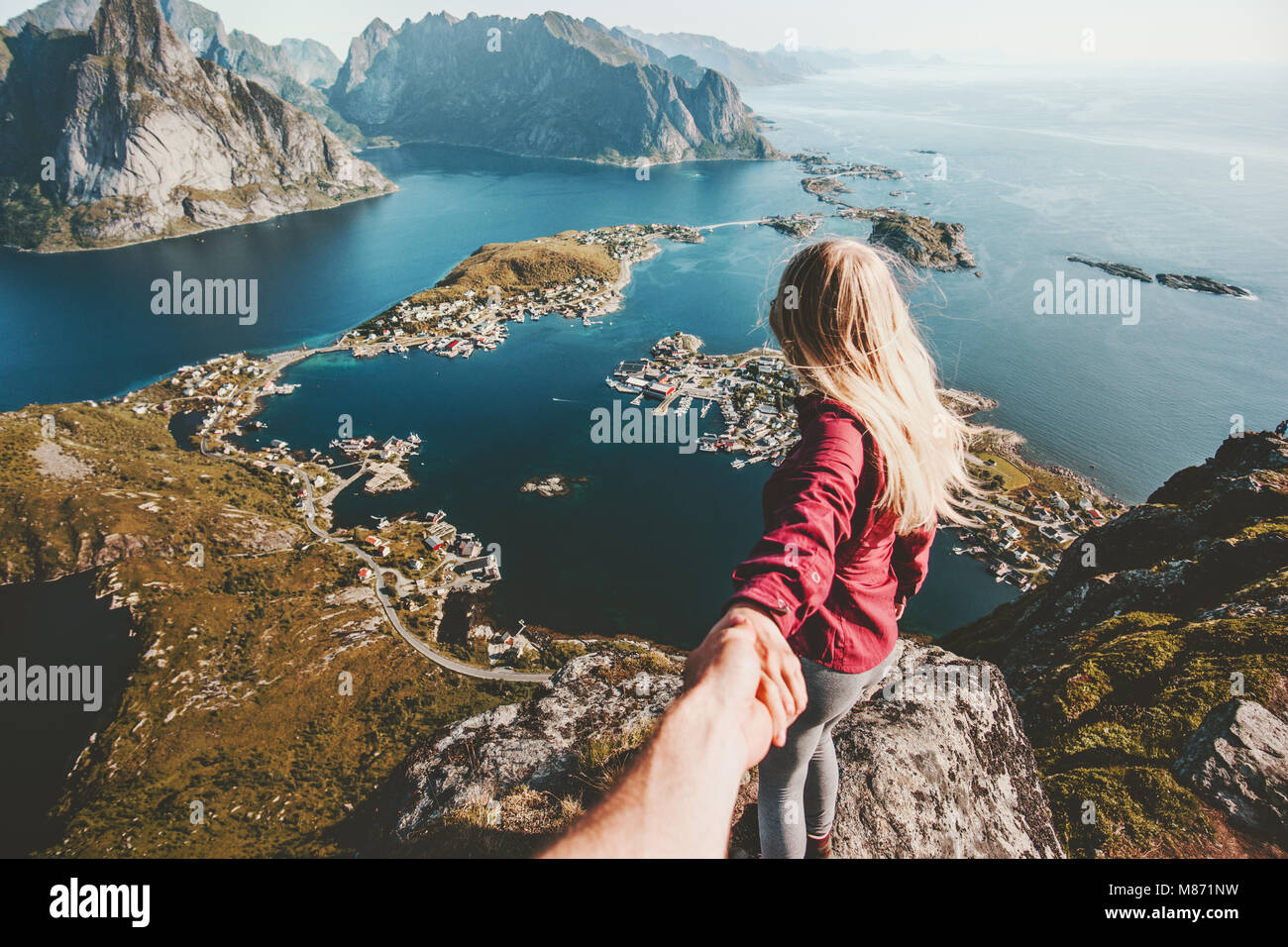 Traveling Couple follow holding hands on cliff mountain in Norway lifestyle concept summer vacations outdoor Lofoten - Stock Image