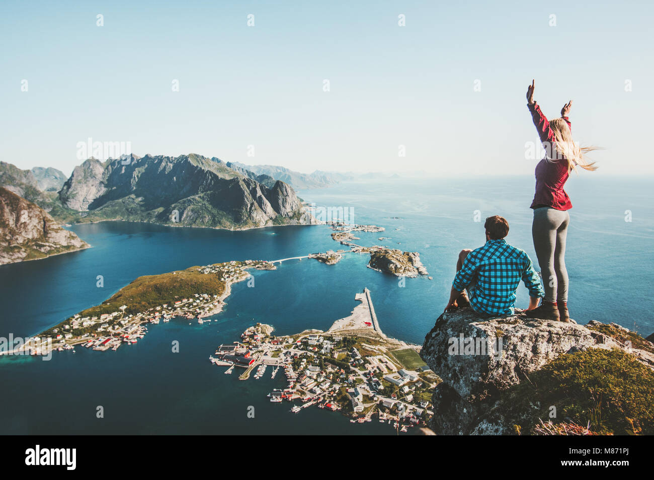Couple travelers traveling together on top cliff Reinebringen mountain in Norway man and woman family lifestyle - Stock Image