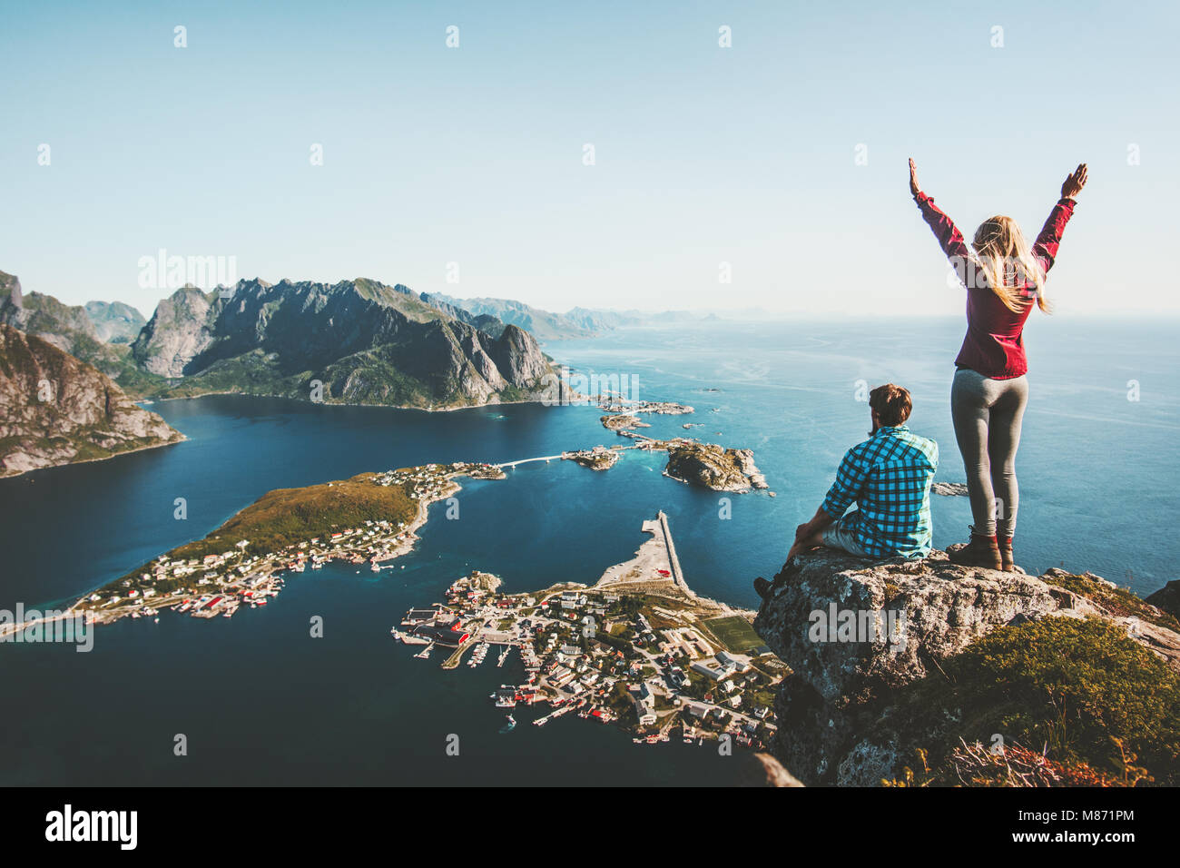 Couple family traveling together on cliff edge in Norway man and woman lifestyle concept summer vacations outdoor - Stock Image