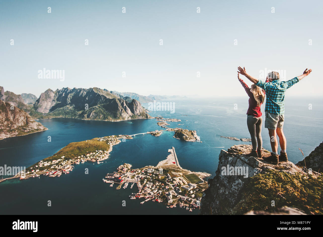 Happy Couple love and travel raised hands on cliff in Norway man and woman family travelers lifestyle concept summer - Stock Image