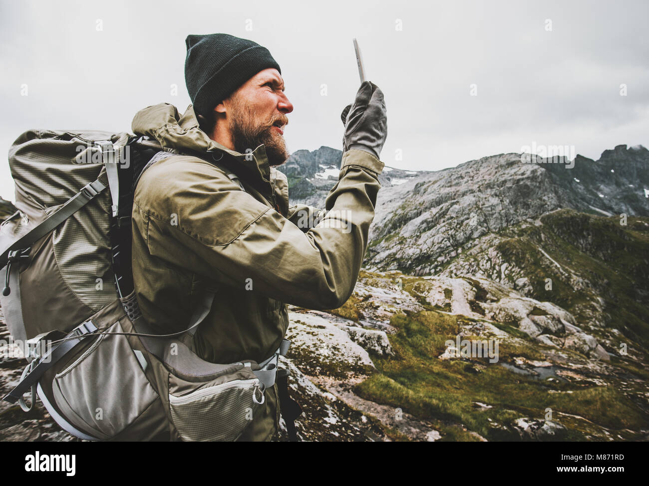 Man traveler using smartphone gps navigator checking location coordinates hiking in mountains with backpack Traveling - Stock Image