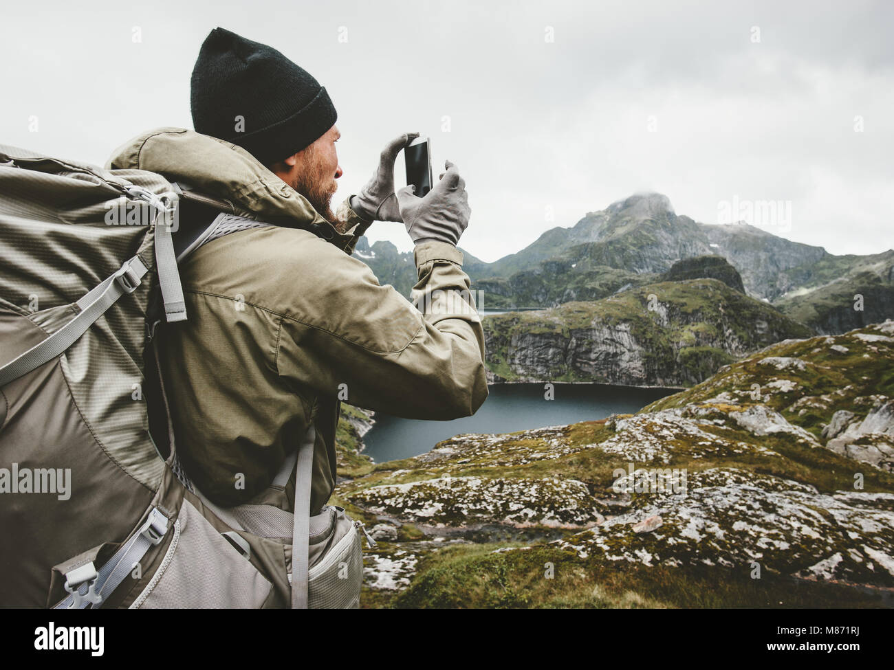 Man traveler checking smartphone gps navigator hiking in mountains Travel survival lifestyle concept outdoor active - Stock Image