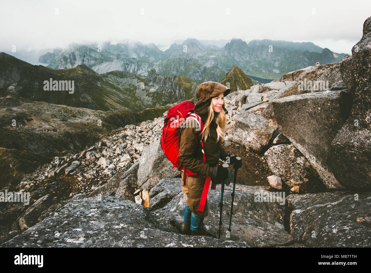 Traveler woman with backpack on Hermannsdalstinden mountain summit in Norway Travel Lifestyle wanderlust concept - Stock Image