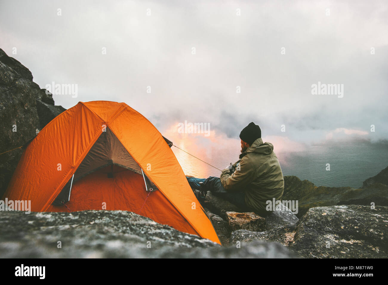 Man traveler relaxing in mountains near of tent camping gear outdoor Travel adventure lifestyle concept hiking active - Stock Image