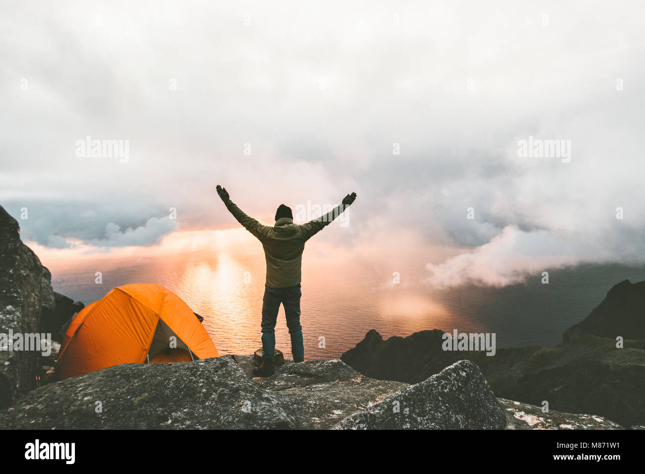 Man traveler happy raised hands on mountain top near of tent camping outdoor Travel adventure lifestyle success - Stock Image