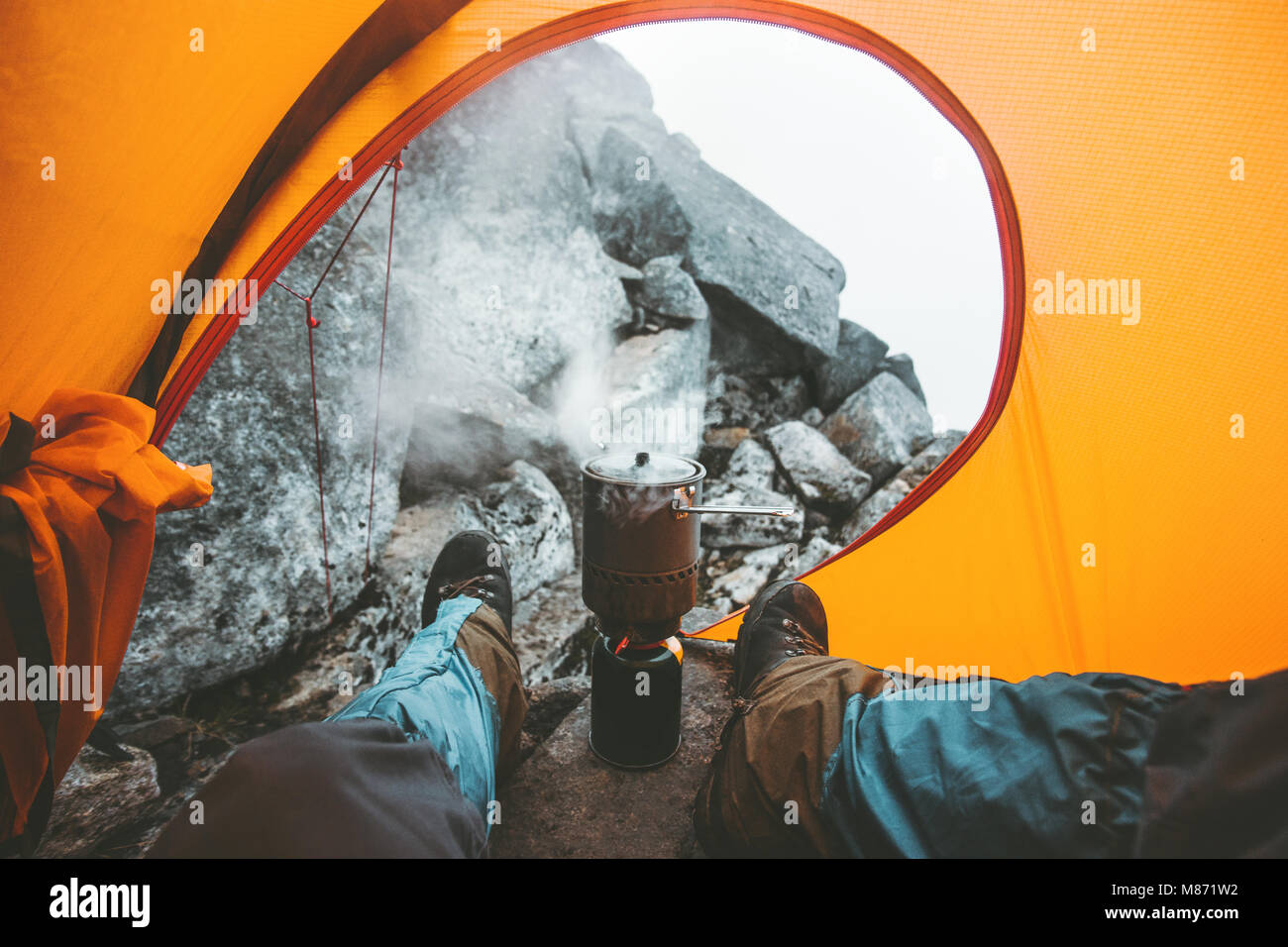 Man traveler cooking in pot on stove burner relaxing in camping tent Travel Lifestyle concept vacations outdoor - Stock Image