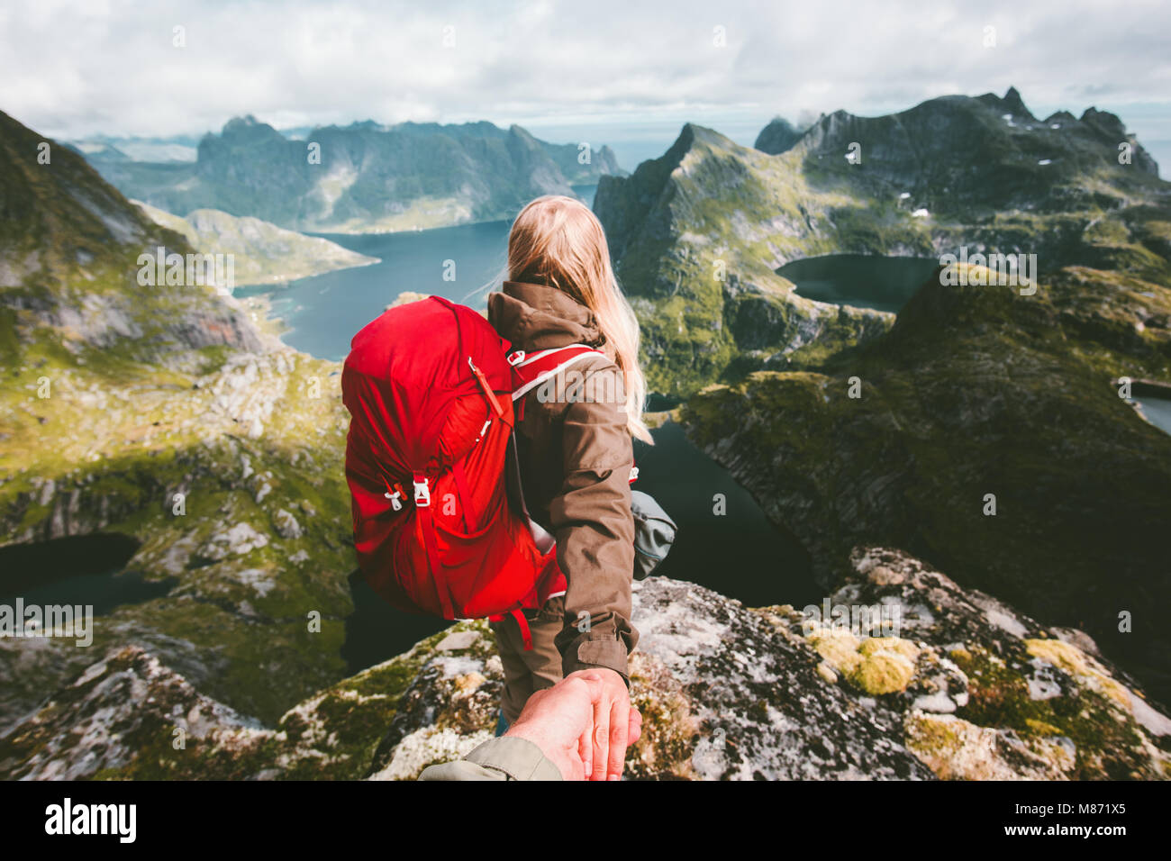 Couple follow holding hands on cliff mountain in Norway Travel lifestyle love emotions concept summer vacations - Stock Image