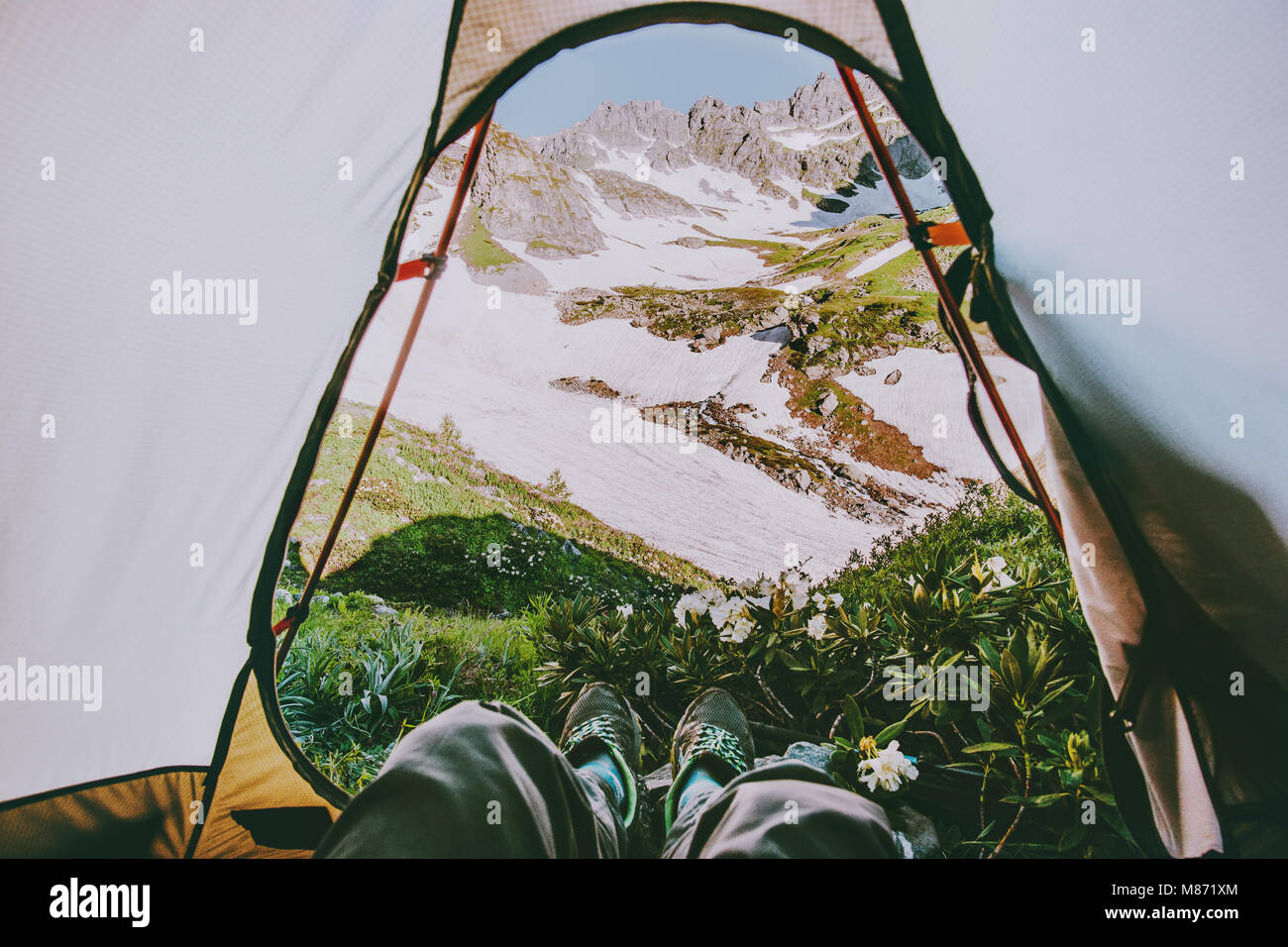 Feet Man relaxing with mountains view from tent camping entrance outdoor Travel wanderlust Lifestyle concept adventure - Stock Image