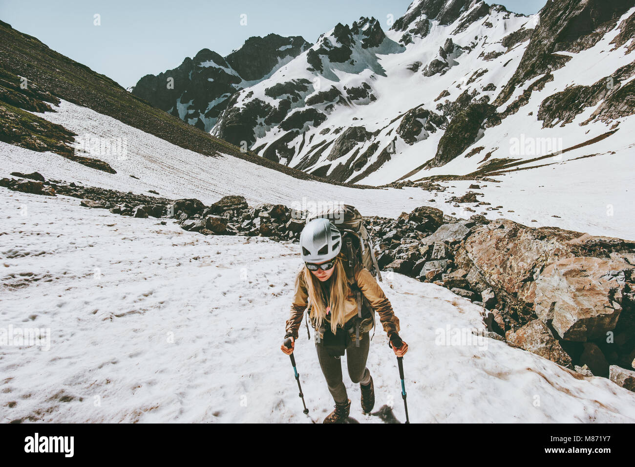 Active woman climbing in snowy mountains Travel lifestyle adventure concept extreme vacations outdoor gear - Stock Image