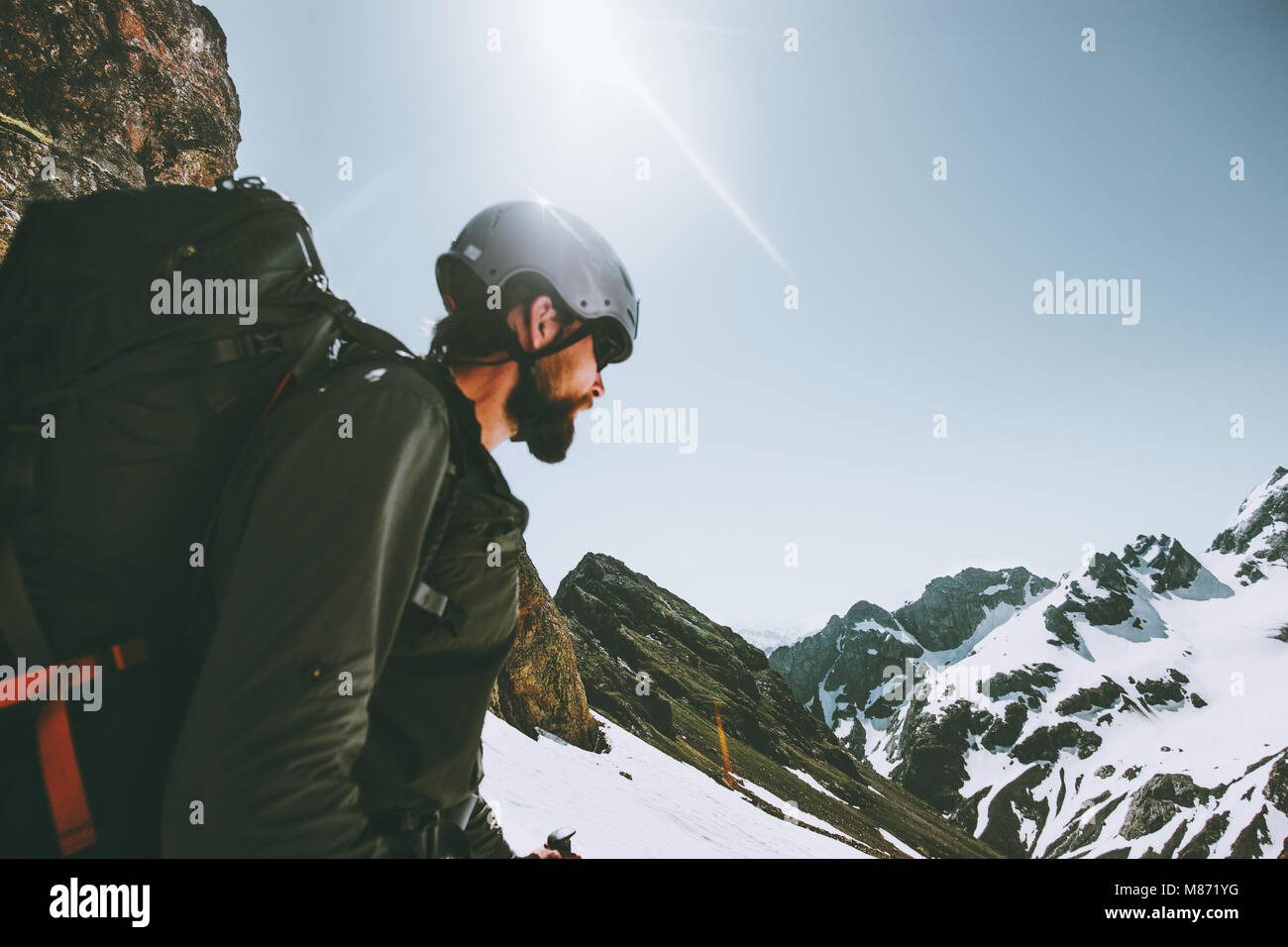 Man adventurer climbing on mountain top Travel adventure lifestyle concept outdoor active extreme vacations - Stock Image