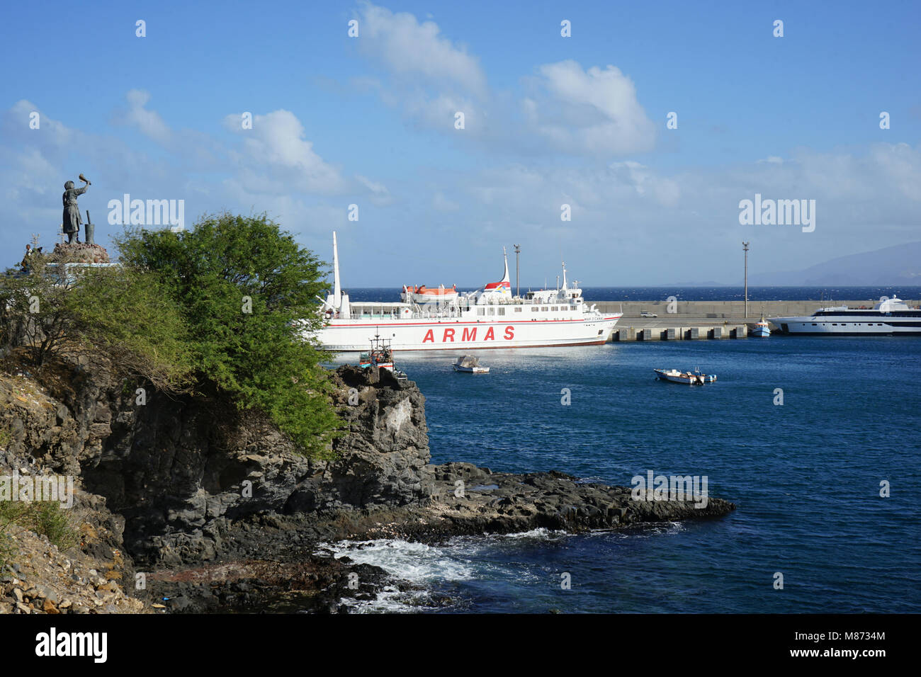 Human Migration Monument, Waving Woman, Ferry and Fishing Boats at the Port of Porto Novo, Santo Antao Island, Cape - Stock Image