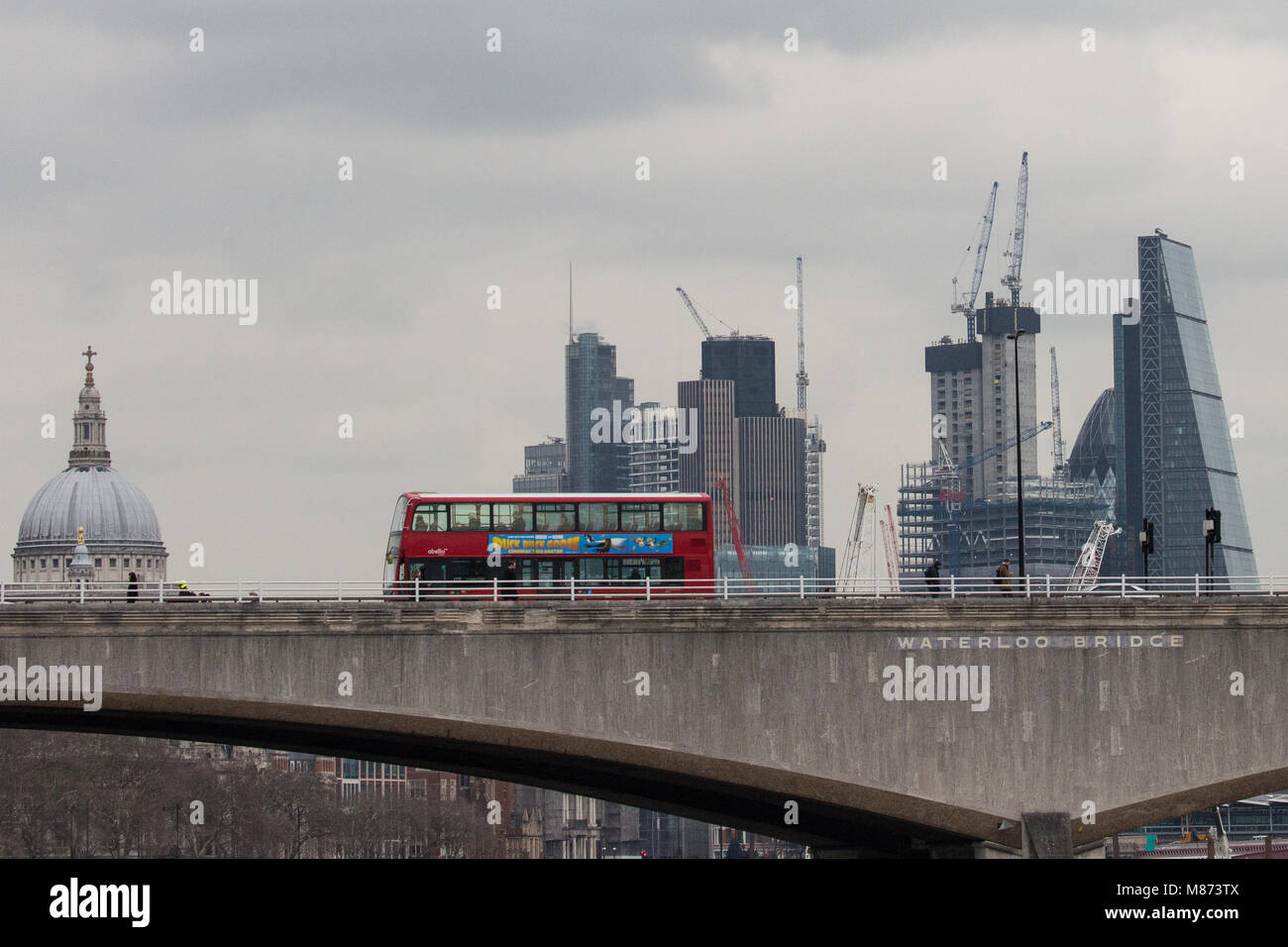 London, UK. 13th March, 2018. A doubledecker bus crosses Waterloo bridge on a cloudy day with St Paul's Cathedral - Stock Image