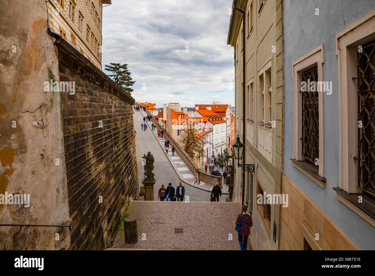 PRAGUE, CZECH REPUBLIC - APRIL 26, 2017: People walking by old streets and stairs of the castle ensemble - Stock Image