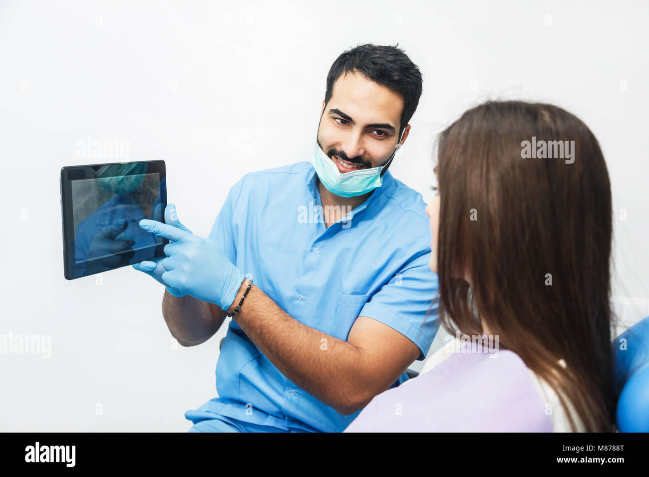 Doctor Shows Teeth X-ray on Tablet - Stock Image