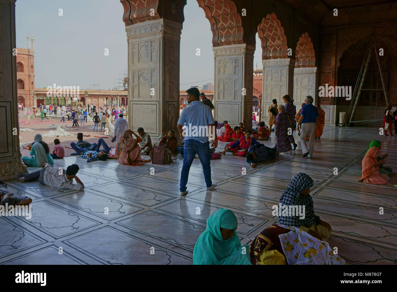 Muslim worshippers praying and relaxing during Friday Prayer, Jama Masjid Mosque, Old Delhi, India Stock Photo