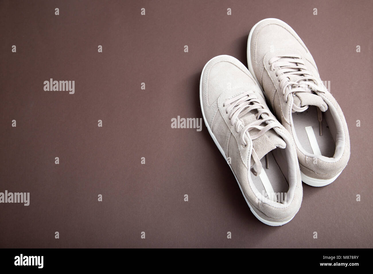 Pastel beige sneakers on a brown background. Flat lay, minimal background. Fashion blog or magazine concept. - Stock Image