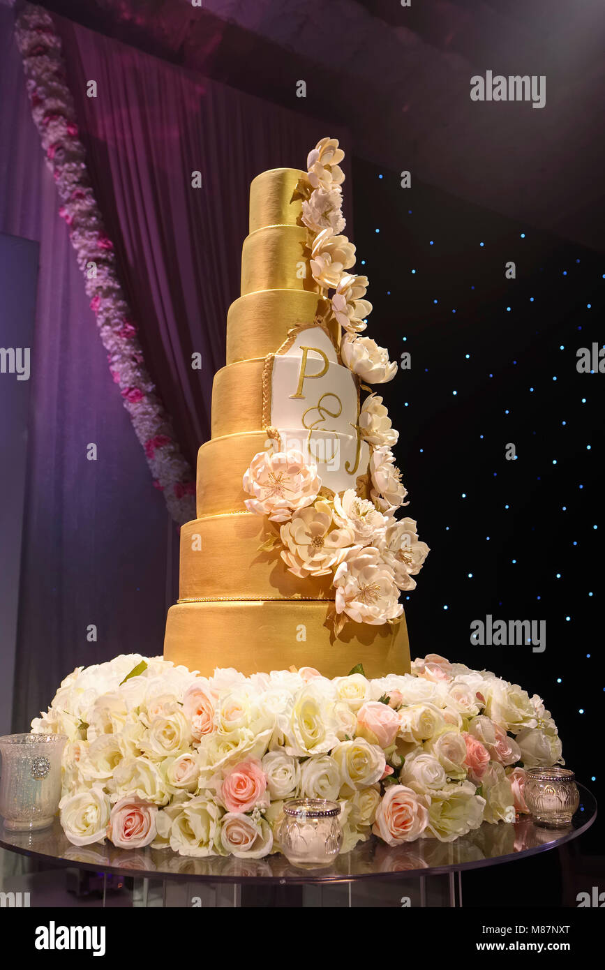 Elaborate tall wedding cake on display at hotel wedding reception - Stock Image
