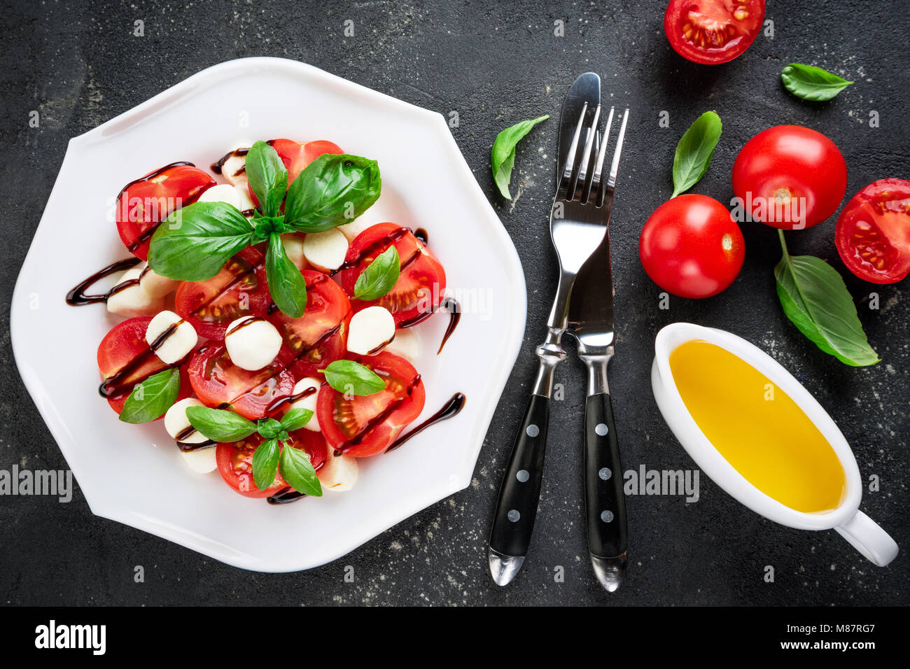 Caprese salad. Tomatoes, mozzarella cheese, tomatoes, olive oil, basil herb leaves, balsamic sauce on dark background. - Stock Image