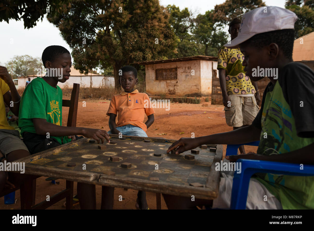 Nhacra, Republic of Guinea-Bissau - January 28, 2018: Group of children playing a game of checkers under a tree Stock Photo