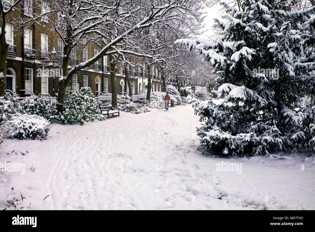 Public park bench victorian houses behind covered with snow London winter - Stock Image