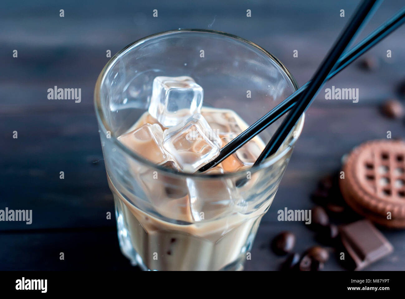 coffee with ice in a glass,milk poured into a glass ice cubes, pieces of chocolate and cookies on a dark wooden Stock Photo