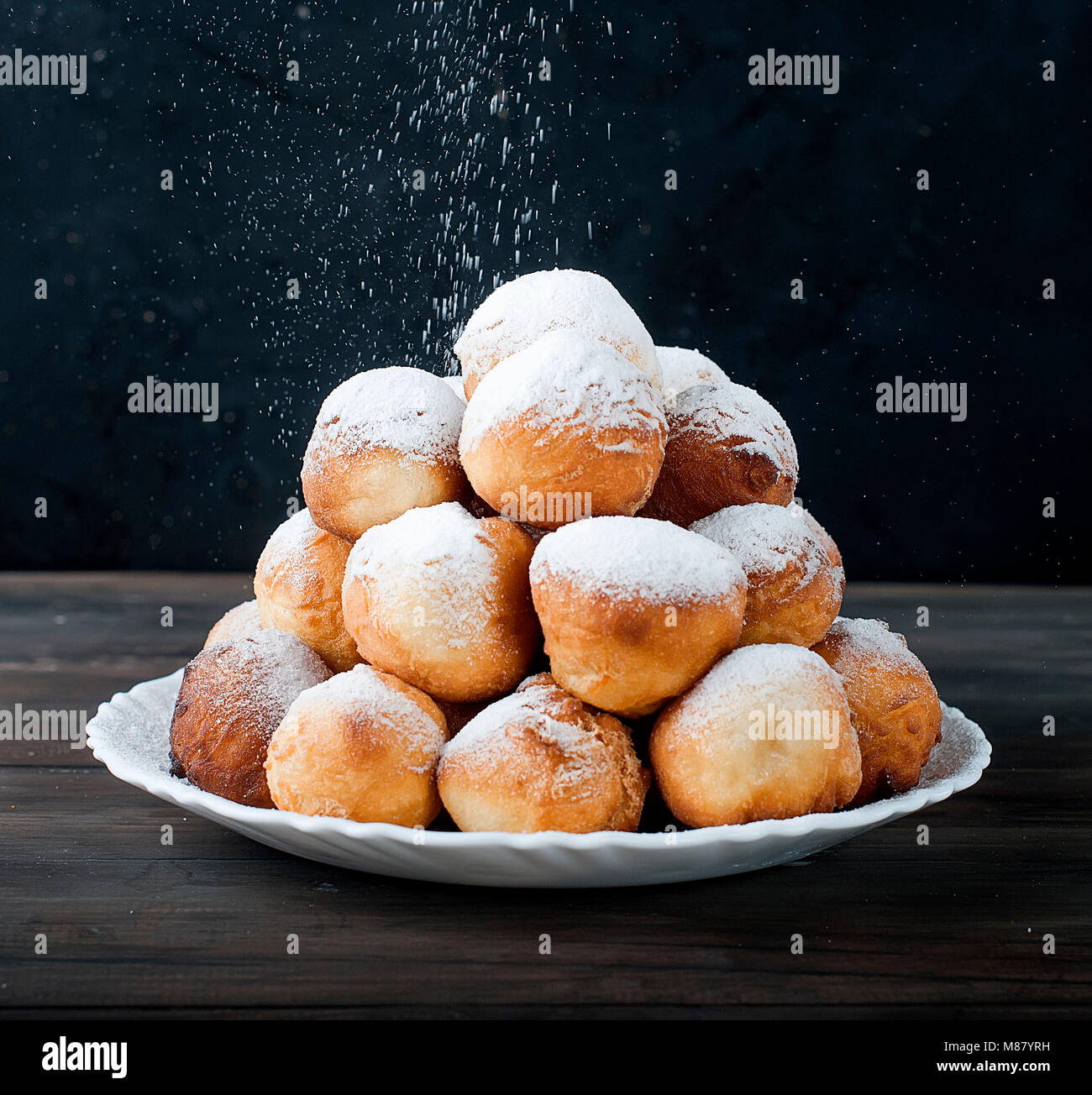 sweet donuts laid out pyramid sprinkled with powdered sugar on the plate ,on dark background , copy space Stock Photo