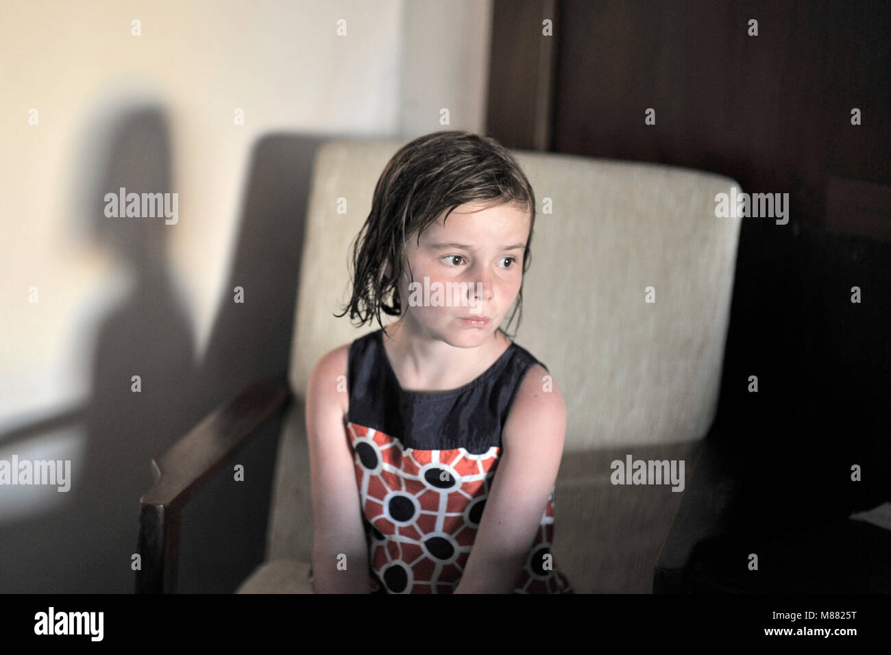 7 year old girl sitting alone with wet hair - Stock Image