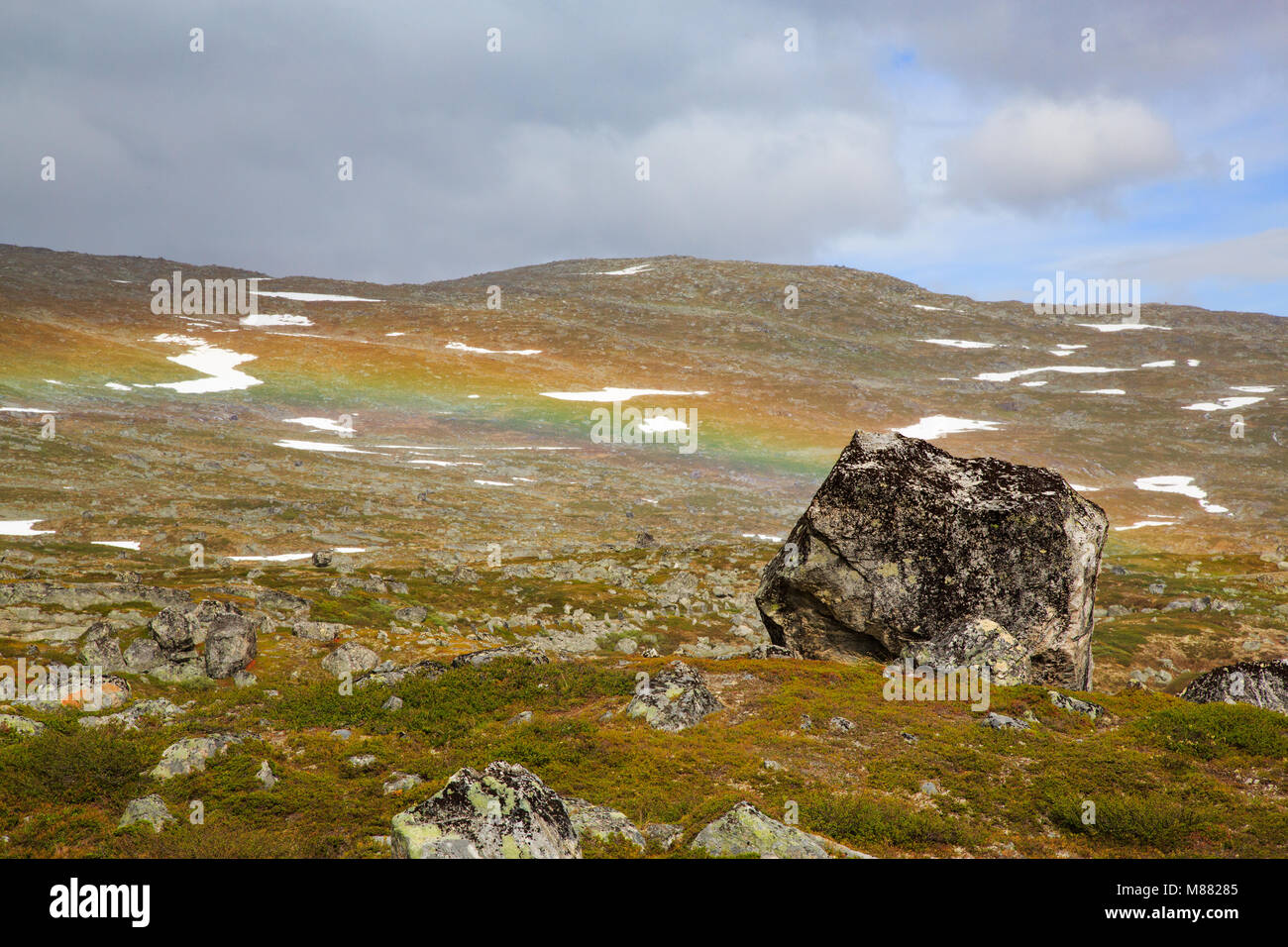 Rainbow seeming to end behind a small rock in the mountain hill Stock Photo