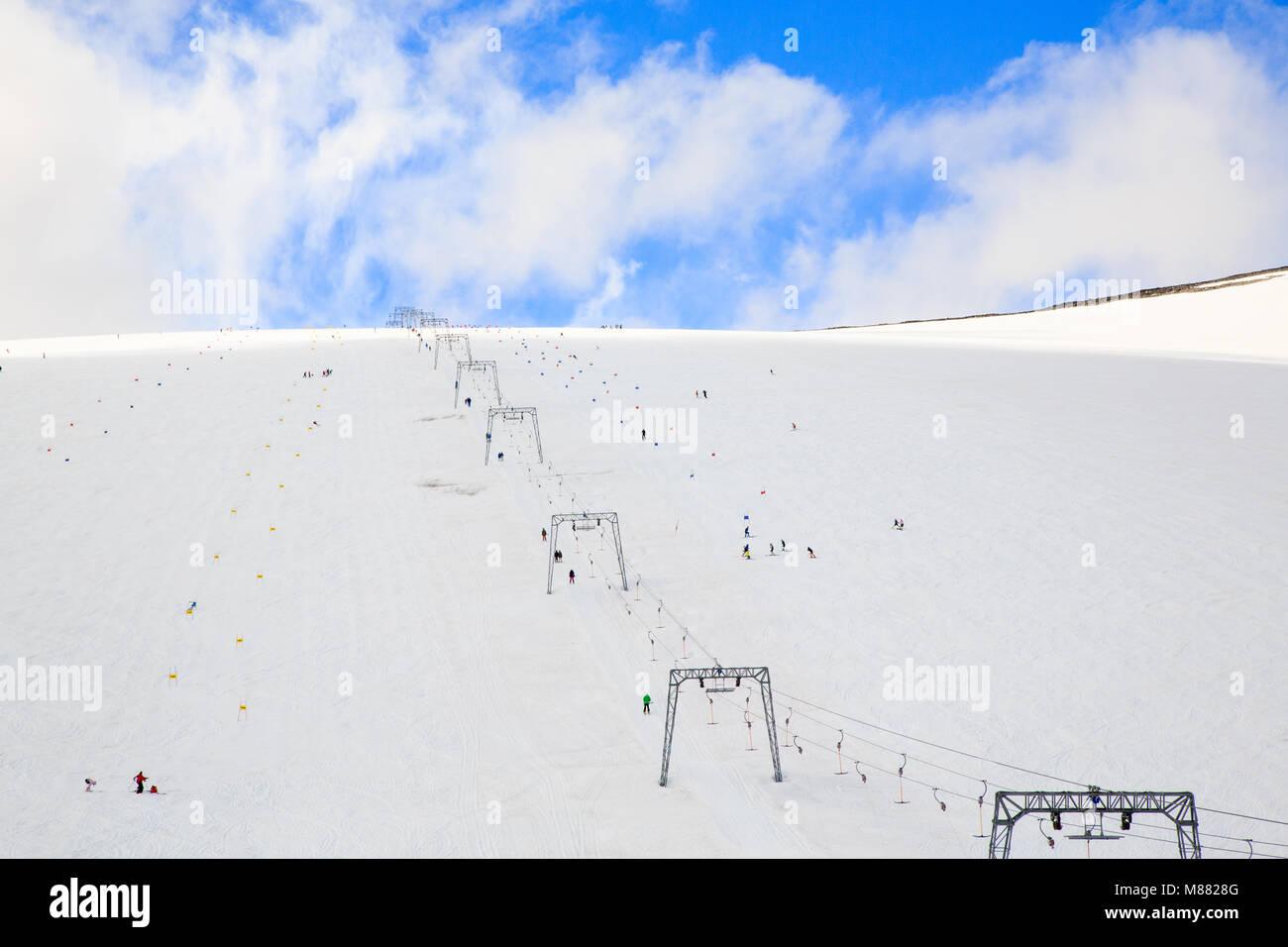 Slalom, snowboard tracks and ski lift up the mountain at Galdhøpiggen summer skiing centre, Juvass Norway - Stock Image