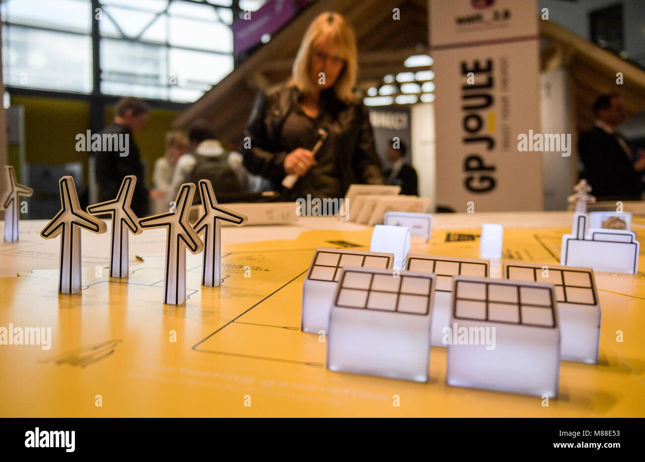 15 March 2018, Germany, Husum: A woman looking at the schematics of an energy supply system at the fair New Energy - Stock Image