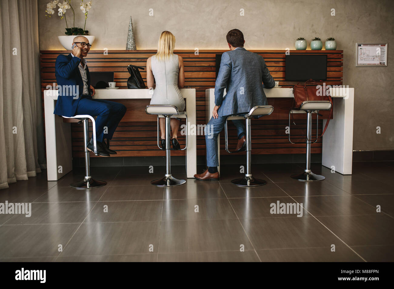 Rear view shot of travelers sitting at free internet service counter in airport. People at cyber corner in airport - Stock Image